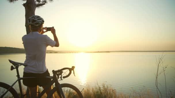 Cyklista stojí pobřeží seaview s kole udělat Foto helmu rychlý pomalý pohyb