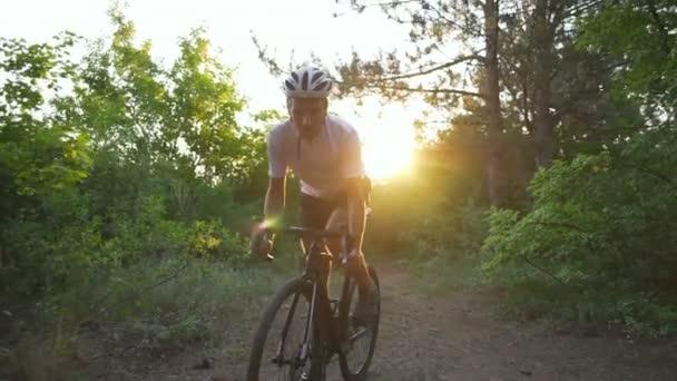 Hezký cyklista jezdí kolo lesní silnici sunrise helmu rychlé zpomalené