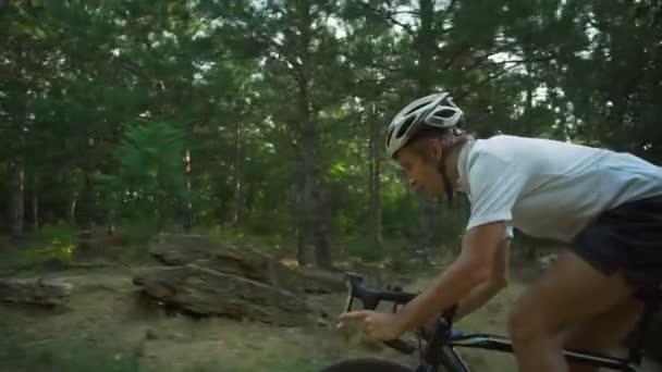 Cyklista jezdit kolo sunny kamenité lesní silnici sunrise helmu rychlé Zpomalený pohyb