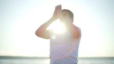 Man and woman practice yoga asanas namaste seaside sunrise rapid slow motion