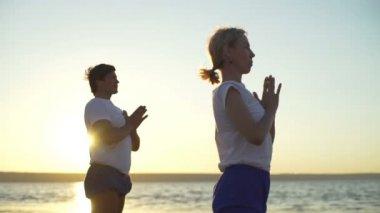 Group of people practice yoga namaste pose seaside sunrise rapid slow motion