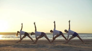 Group of young people practicing yoga seaside sunrise rapid slow motion