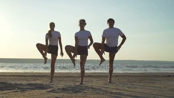 group of three people doing yoga tree pose seaside sundown rapid
