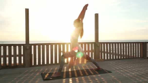 Flexibilní běloška dívka praxe bojovník jóga póza na střeše ve slunečním svitu