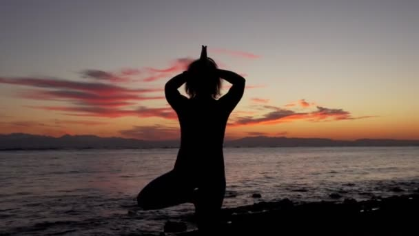 Silhouette of woman practicing tree yoga pose on sea coast at sunset