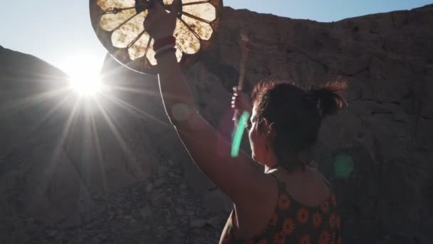 Unrecognizable woman playing tambourine in sun glare in mountains sunset