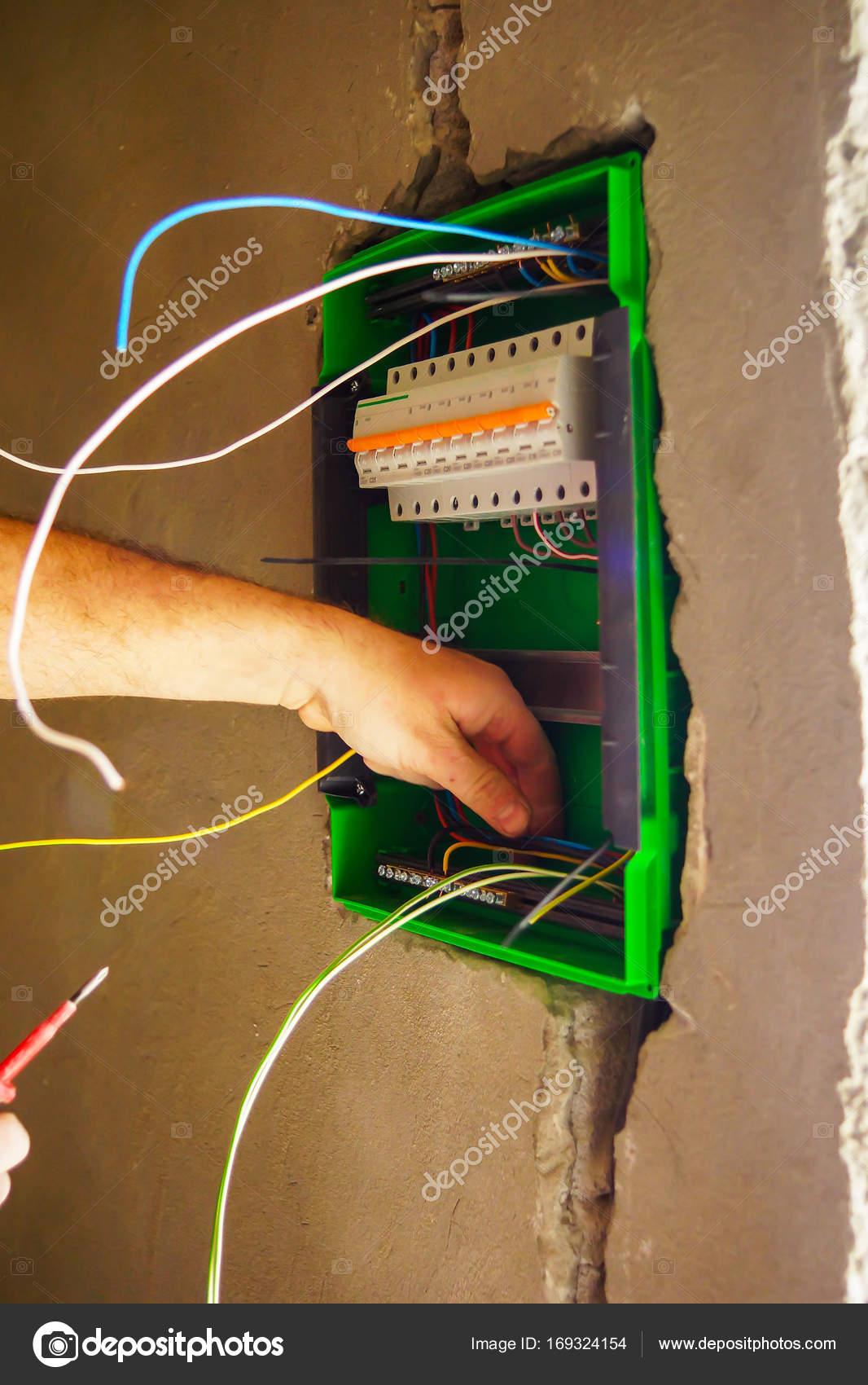 Elektrische Verdrahtung Hände wird durch das Loch in der Wand der ...