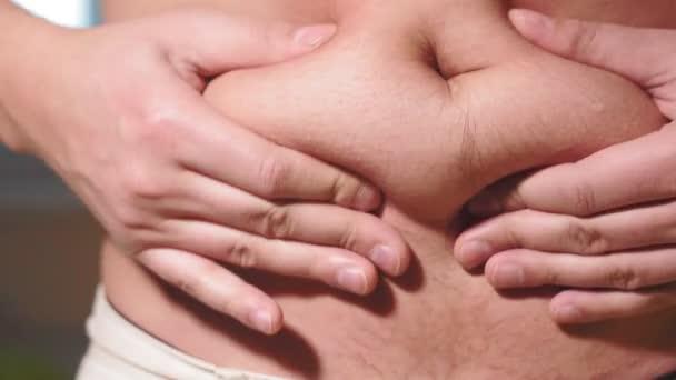 mladý běloch se chytá za tlusté břicho. břišní tuk, hubnutí, nadváha