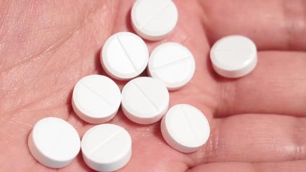 weiße runde Pillen in der Hand eines Mannes in Großaufnahme. medizinisches Konzept