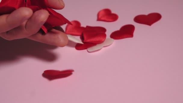ruka klade srdce na růžové pozadí