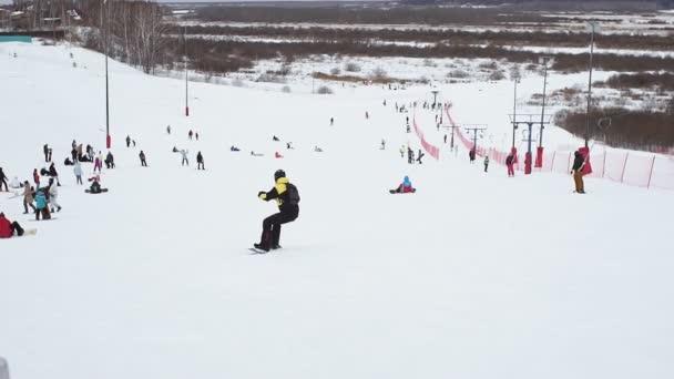 V zimním lyžařském středisku lidé lyžují a jezdí na snowboardu po zasněžených svazích. Lyžařský vlek na sněhové hoře. Zimní aktivita