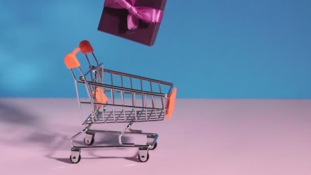 dárky v nákupním košíku na modrém růžovém pozadí. Abstraktní designový prvek, roční prodej, koncept nákupní sezóny.