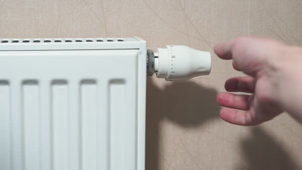 man hand adjusting temperature thermostat on radiator.