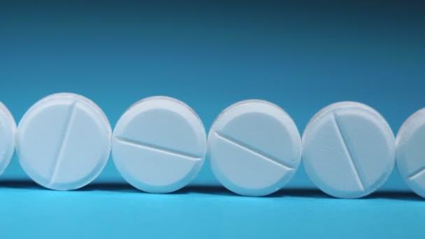 runde weiße Tabletten in der Hand, Nahaufnahme auf blauem Hintergrund mit Platz für Text oder Bild. Tabletten gegen Hautalterung