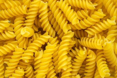 Fusilli helix shaped Macaroni Pasta raw food background or texture close up