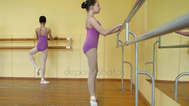 Dívky v fialová sportovní gymnastiky plavky a bílý balet boty na staré dřevěné podlahy v blízkosti barre nebo baletní tyče během výcviku balet. Součástí taneční cvičení.