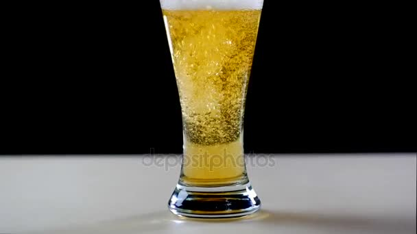 Bier ergießt sich in Glas auf schwarzem Hintergrund. Blasen und Schaum im Bierglas. Schaum, der das Bierglas herunterrutscht. Bier ins Glas füllen. Bierblasen. Bier in Glas auf schwarzem Hintergrund gegossen.