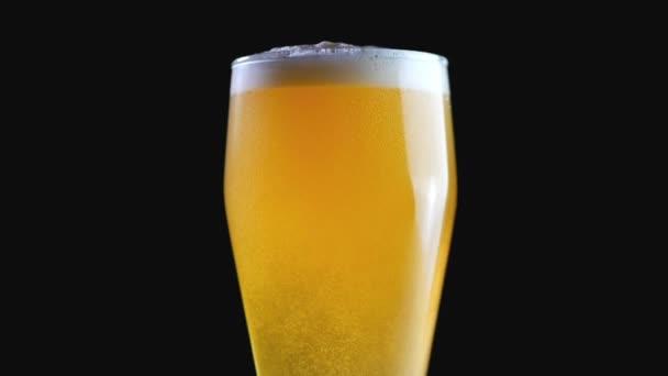 Pouze vařené pivo jantarové. Pivo z bee-eater. Pivo na černém pozadí. Bubliny a pěny ve sklenici piva. Použijete-li pivo ve sklenici. Pivní bubliny. Zpomalený pohyb