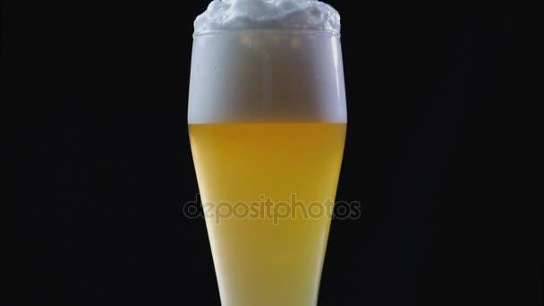 Bierblasen. Bier wird auf schwarzem Hintergrund ins Glas gegossen. viel Schaum.