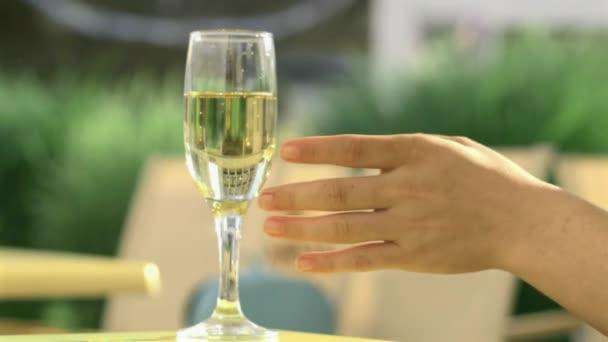 Ruka na skleničku šampaňského. Bubliny detail. 4k