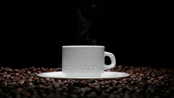 coffe cup and coffe beans. A white cup of evaporating coffee on the table with roasted bean. A cup with coffe bean as background 4k