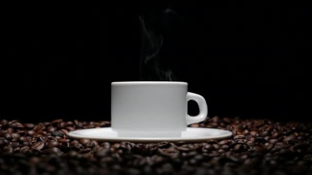 Coffe hrnek a coffe fazole. Bílý hrnek odpařovací kávu na stůl s pražených bobů. Pohár s coffe bean jako pozadí 4k