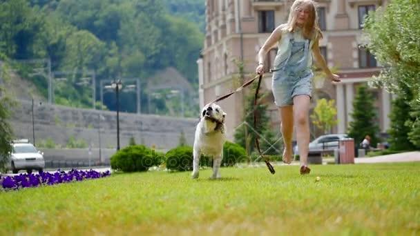 die kleine schwester rennt der schwester mit dem hund hinterher.. ein jugendliches mädchen spielt mit ihrem lieblingshund im park. Er ist ein treuer Freund des Menschen.