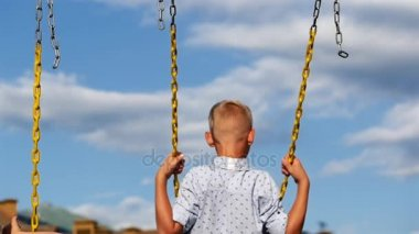 Dreams, summer. The family enjoys the summer, walks. The boy is riding on a swing. Slow moshion.