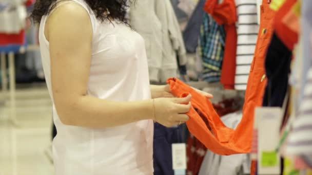 Atraktivní bruneta zvolí kombenizon pro malou dceru v úložišti. Krásná žena v obchod s oblečením pro děti. Krásná žena nakupuje oblečení v obchodě