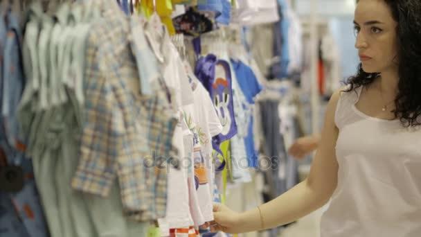 ab2d6c4e6 Atractiva señora morena elige ropa interior en la tienda. Pijamas de mujer  hermosa en el supermercado. Linda mujer compra ropa en centro comercial–  metraje ...