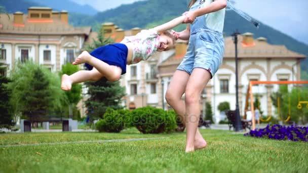 Dvě sestřičky rádi dívky hrát zábavné na zelené trávě v létě