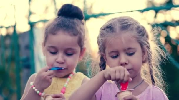 Two little girls girlfriends with curly blonde hair with blue eyes eating ice cream and laughing.