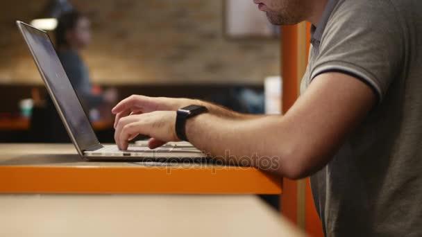 Mladý podnikatel pracuje na počítači, v kavárně. 4k.