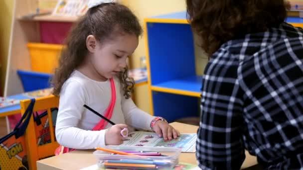 Der Lehrer und die Schülerin der Frau sitzen mit dem Buch am Tisch. der Schüler beantwortet die Frage des Lehrers richtig und erhält Dankbarkeit.
