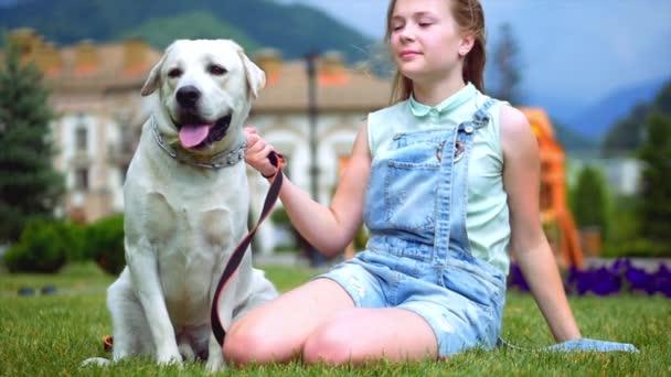 Ein Teenager-Mädchen umarmt ihren Hund im Park. der hund leckt und küsst das mädchen.. ein jugendliches mädchen spielt mit ihrem lieblings hund im park. Er ist ein treuer Freund des Menschen.