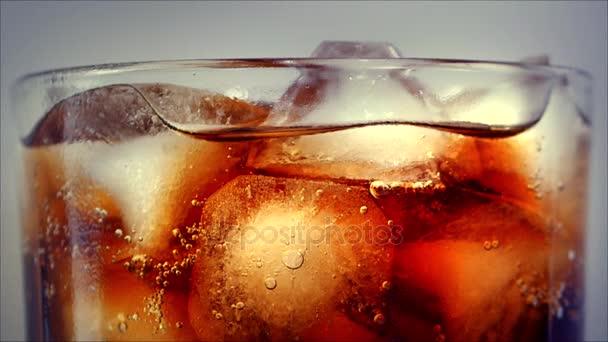 Cola s pozadím kostky ledu. Colu s ledem a bubliny ve skle. Closeup sodu. Jídlo na pozadí. Začátkem plné Hd video záznam 4k