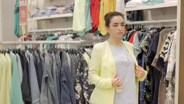 Atraktivní tmavovláska zvolí sako vypadá v zrcadle. Krásná žena brunetka kupuje oblečení v obchodě. Krásná žena s hnědými vlasy se snaží na nové sako v zkušebna oblečení boutique.