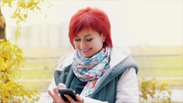 Herbst. Attraktive Frau mit kaukasischen Augen mit feurigen Haaren auf der Straße Jubel nutzt ein Handy