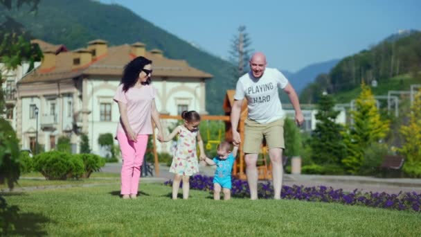 Carefree young Caucasian family happily runs along the green grass holding hands, happy faces of the family.