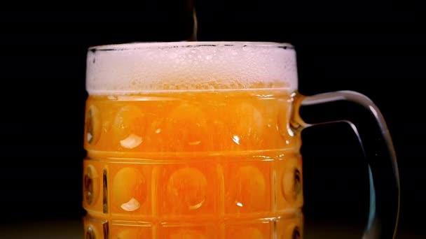Pivo se nalije do sklenice na černém pozadí. Pěna rychle snímky přes sklo. Extrémní velké pivní pěny a bublin. Plný hrnek tmavého piva na černém pozadí. Zpomalený pohyb