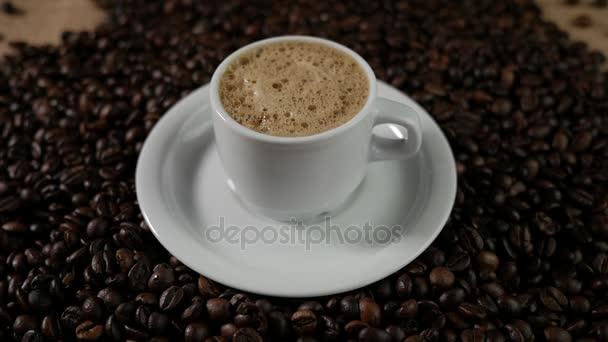 Šálek kávy a kávových zrn. Bílý šálek kávy odpařovací pěnou na stůl s restovanými fazolkami