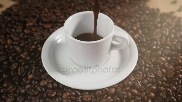 Csésze kávé- és babkávé. Egy fehér kupa párolgó kávé az asztalra és sült bab. Lassú mozgás kávé pour.
