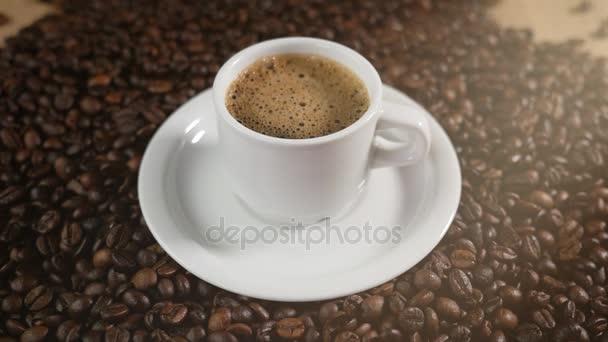Šálek kávy a kávových zrn. Bílý šálek kávy odpařovací pěnou na stůl s restovanými fazolkami.
