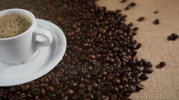 Coffee cup and coffee beans. A white cup of evaporating coffee on the table with roasted bean. Slow Motion coffee pour.