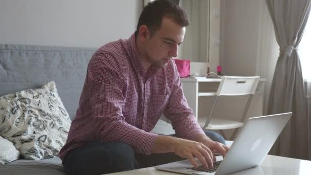 Člověk pracuje z domova pomocí horní a trackpad. Mladý podnikatel u stolu pití kávy, dělá práci na počítači. 4k