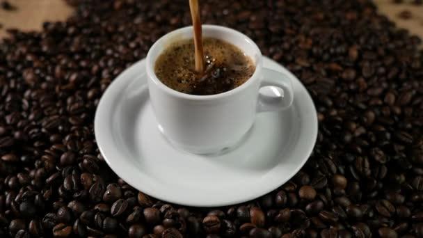 Šálek kávy a kávových zrn. Bílý hrnek odpařovací kávu na stůl s pražených bobů. Slow Motion káva pour.