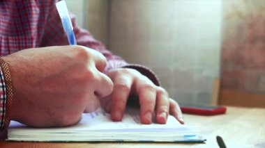 Hands writing on the paper.Young business man sitting at table drinking coffee, doing work writes in a book. Stock footage.