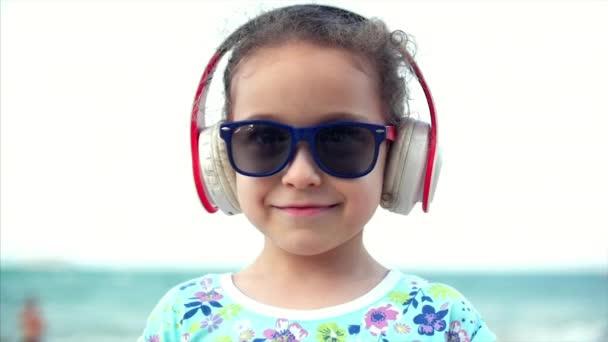 494fecd51 Menina feliz na praia usando óculos escuros, ouvindo música em fones de  ouvido, olhando para a câmera, sorridente e um pouco tímida. Criança,  crianças ...