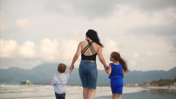 Mladá rodina, matka a děti jsou procházky podél pobřeží. Šťastná rodina chůzi na pobřeží moře.