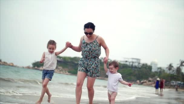 Bambini, la madre e la famiglia giovane procede a piedi lungo la costa. Famiglia felice che cammina sul litorale di mare